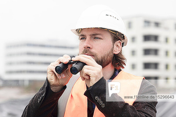 Mid adult male civil engineer holding binoculars on construction site