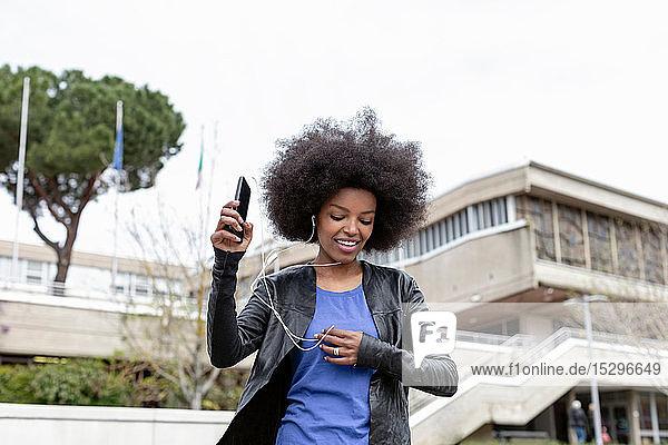 Junge Frau mit Afro-Haaren in der Stadt  die spazieren geht und Smartphone-Musik hört