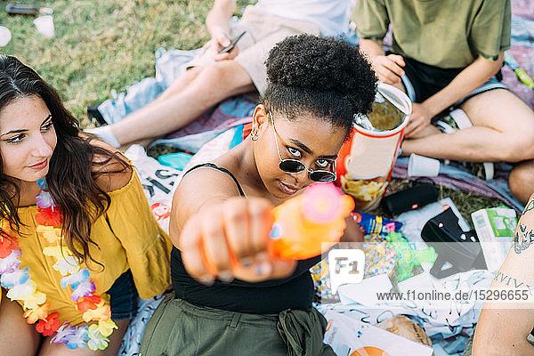Junge Frau beobachtet Freund  der beim Picknick mit der Wasserpistole zielt