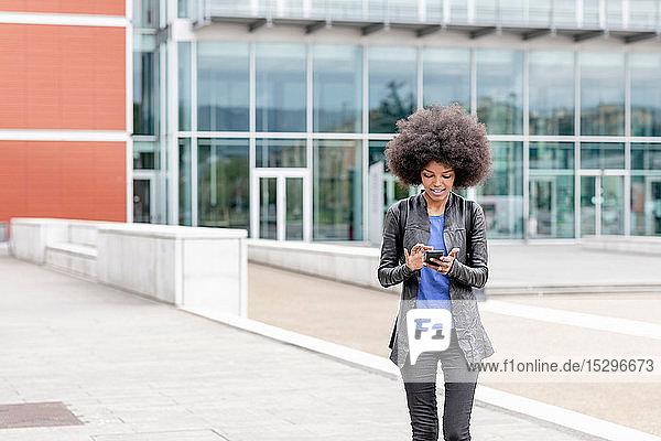 Junge Frau mit Afro-Haaren in der Stadt  die den Touchscreen eines Smartphones benutzt