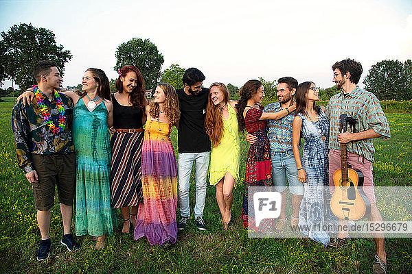 Eine große Gruppe glücklicher junger Erwachsener steht auf dem Feld und umarmt sich gegenseitig