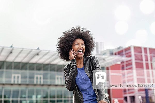 Glückliche junge Frau mit Afrofrisur in der Stadt  die lacht und mit einem Smartphone telefoniert