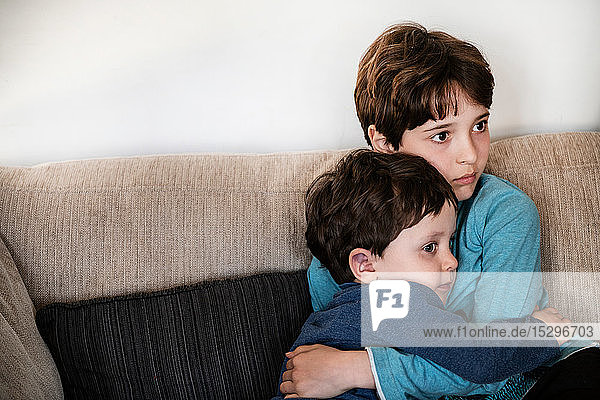 Großer Bruder umarmt Kleinkind  starrt ungläubig auf Sofa