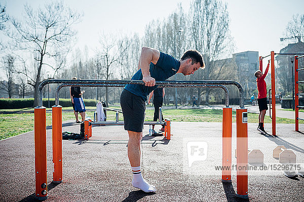 Calisthenics at outdoor gym  young man preparing to use parallel bars  full length