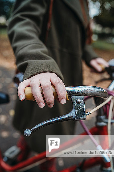 Young woman pushing bicycle in autumn park  close up of hand on handlebar