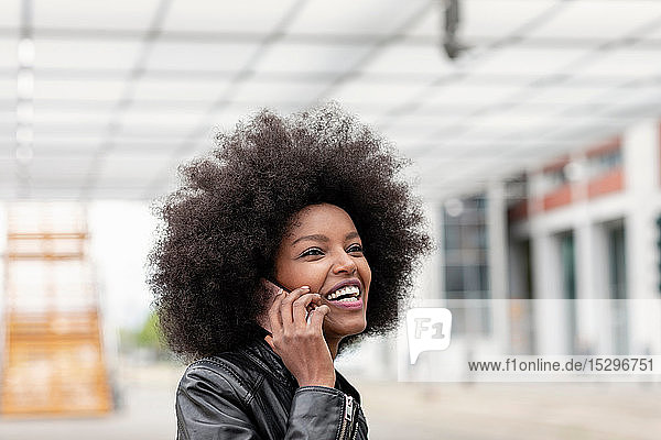 Junge Frau mit Afro-Haaren am Stadtbahnhof telefoniert mit einem Smartphone