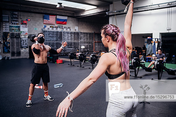 Young woman and man training  lifting dumbbells in gym