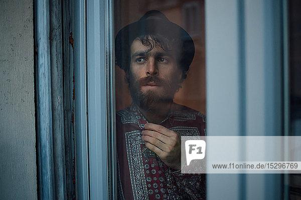 Bärtiger junger Mann in tiefem Nachdenken am Fenster