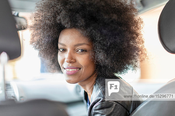 Happy young woman with afro hair in car passenger seat  portrait