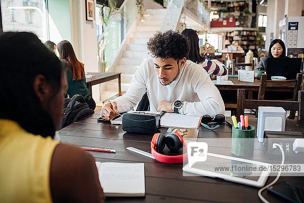 Junger Geschäftsmann und Frau arbeiten fernab am Cafétisch