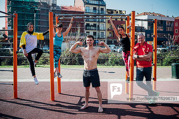 Calisthenics class at outdoor gym  men and women posing on exercise equipment  portrait