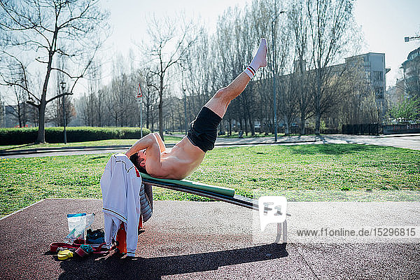 Calisthenics at outdoor gym  young man on weights bench with legs raised