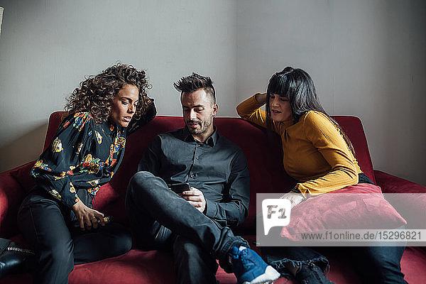 Freunde benutzen Smartphone auf dem Sofa