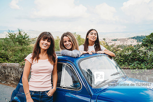 Woman standing beside friends posing in car sunroof  Florence  Toscana  Italy