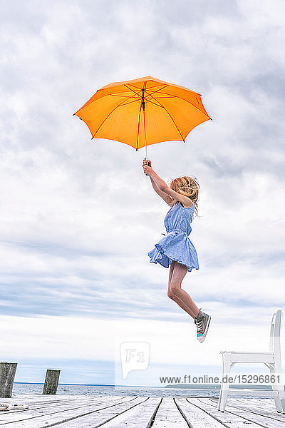 Girl being lifted off her chair by umbrella