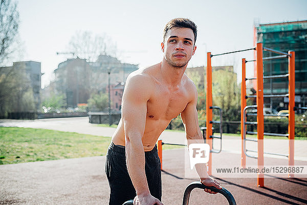 Calisthenics at outdoor gym  bare chested young man preparing to use exercise equipment
