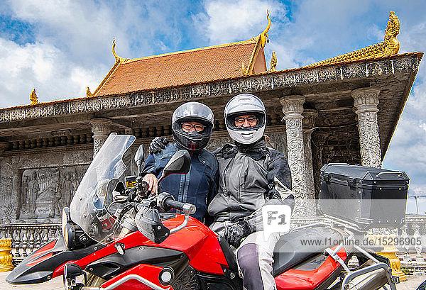 Bikers posing on ADV motorbike in front of buddhist temple  Phnom Penh  Cambodia
