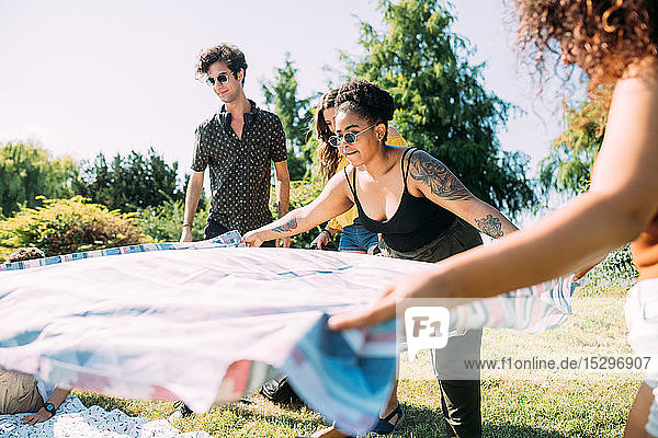 Freunde legen Picknickdecke im Park aus