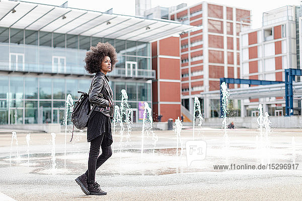 Coole junge Frau mit Afro-Haaren in der Stadthalle  in voller Länge