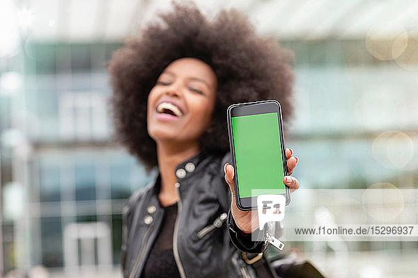 Junge Frau mit Afrofrisur in der Stadt  lacht und hält Smartphone hoch