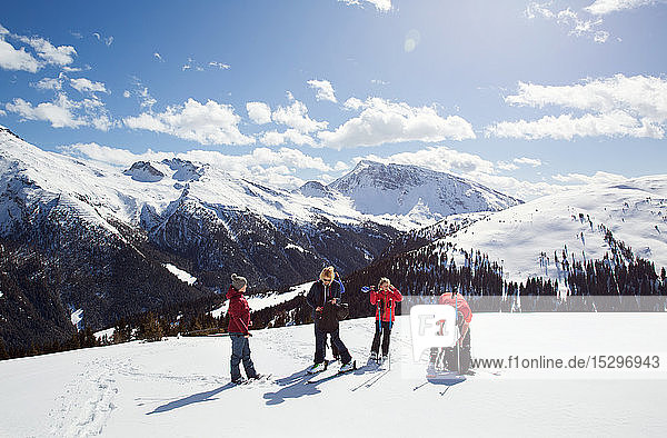 Mature woman and daughters taking a break while snowshoeing on snow covered mountainside  Styria  Tyrol  Austria