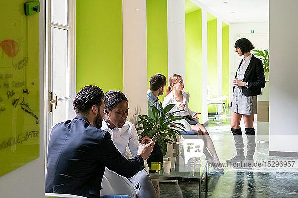 Junge männliche und weibliche Unternehmensgründer treffen sich in einem Großraumbüro