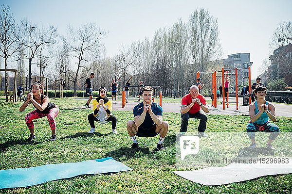 Calisthenics class at outdoor gym  women and men practicing yoga squatting pose