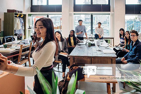 Junge Geschäftsfrau macht Präsentation für Kollegen