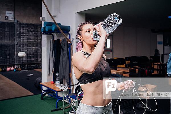 Junge Frau trainiert  trinkt Flaschenwasser im Fitnessstudio
