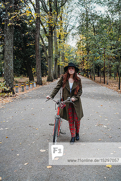 Young woman with long red hair pushing bicycle in tree lined autumn park  portrait  Florence  Tuscany  Italy
