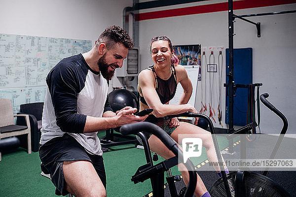 Junge Frau und Mann trainieren gemeinsam auf Fitness-Fahrrädern  Blick auf Smartphone