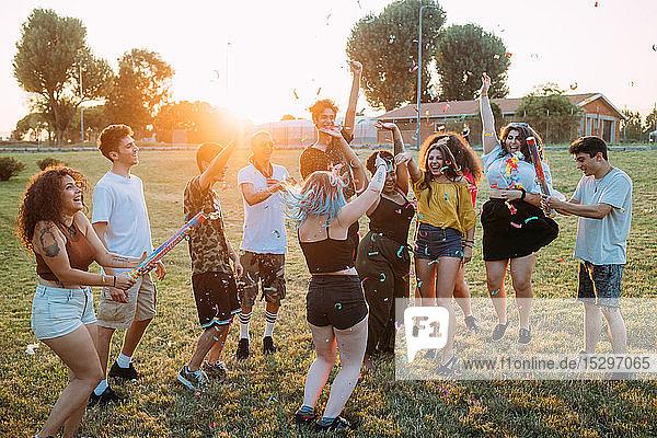 Gruppe von Freunden spielt mit Konfetti im Park
