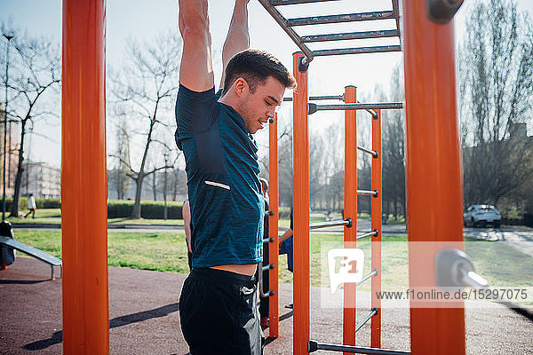 Calisthenics at outdoor gym  young man hanging from exercise equipment