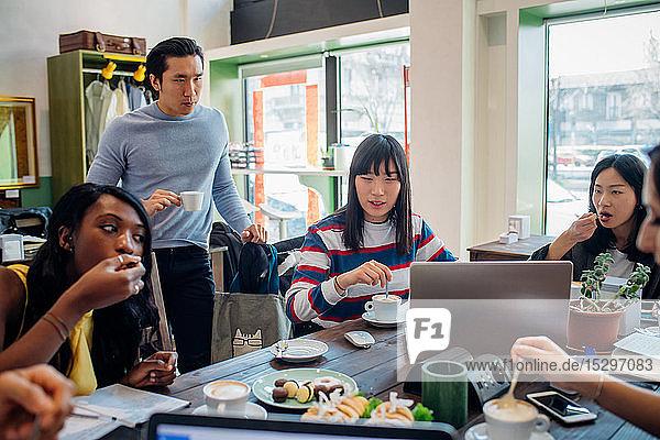 Junges männliches und weibliches Geschäftsteam beim Arbeitsessen am Café-Tisch