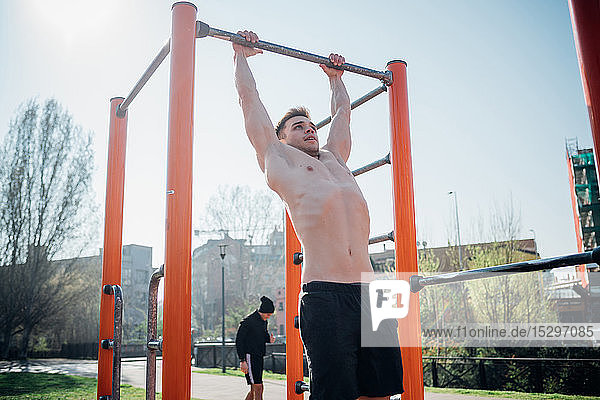 Calisthenics at outdoor gym  bare chested young man hanging from exercise equipment