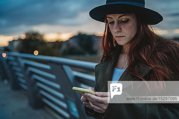 Young woman with long red hair on footbridge looking at smartphone at dusk  Florence  Tuscany  Italy