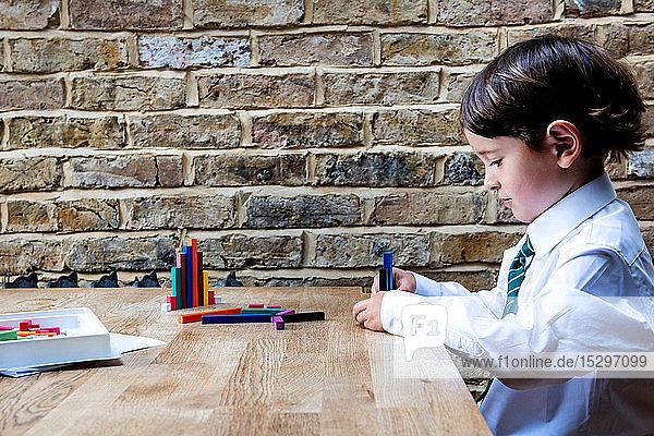 Junge in Schuluniform spielt zu Hause mit farbigen Stöcken