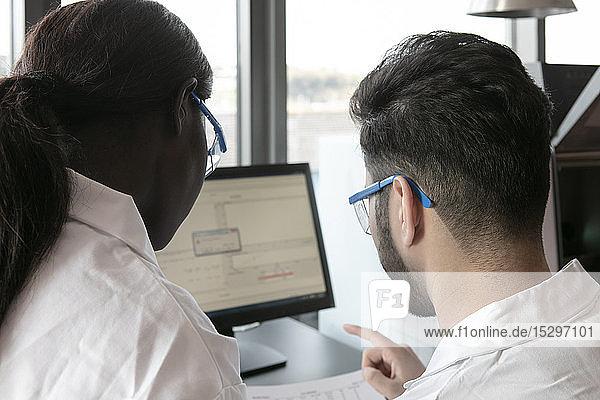 Junge Wissenschaftlerinnen und Wissenschaftler betrachten Papierkram und Computer im Labor  Blick über die Schulter