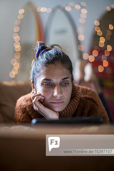 Junge Frau auf Wohnzimmersofa liegend und auf Laptop starrend  flacher Fokus