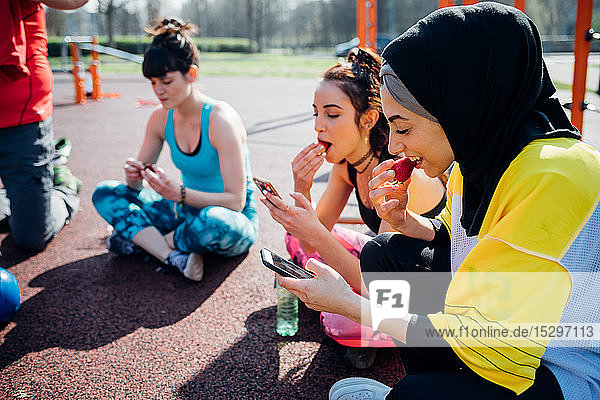 Calisthenics class at outdoor gym  young women sitting looking at smartphones and eating fruit