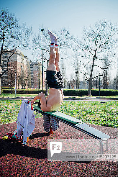 Calisthenics at outdoor gym  young man upside down on weights bench