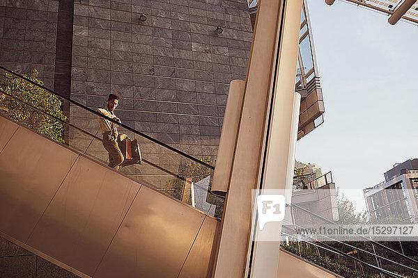 Businessman descending escalator of office building  Milano  Lombardia  Italy