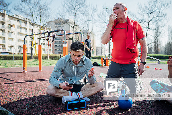 Calisthenics class at outdoor gym  men sitting looking at smartphone and eating fruit