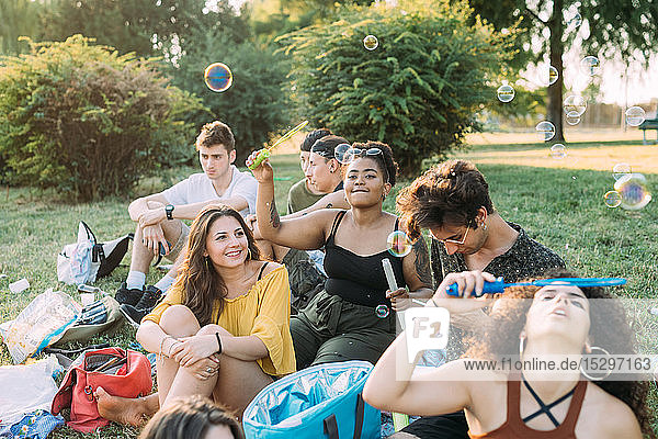 Group of friends relaxing  blowing bubbles at picnic in park