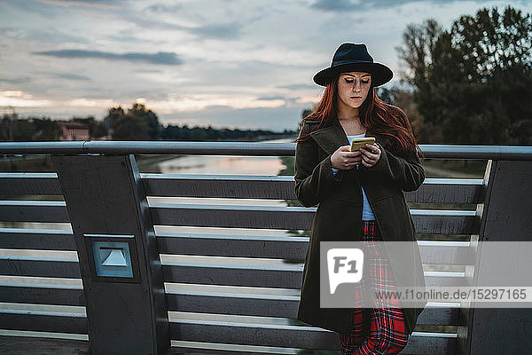 Young woman with long red hair leaning on footbridge looking at smartphone at dusk  Florence  Tuscany  Italy