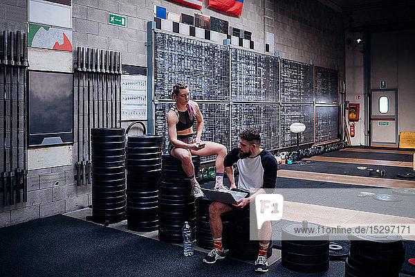 Junge Frau und Mann trainieren gemeinsam im Fitnessstudio  auf Gewichten sitzend mit Smartphone und Laptop