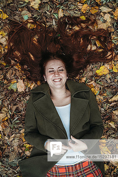 Young woman with long red hair lying amongst autumn leaves laughing  overhead view