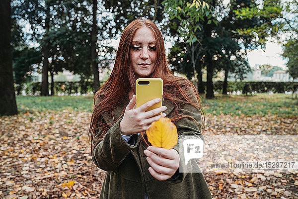 Young woman with long red hair in park taking smartphone photo of her hand holding autumn leaf
