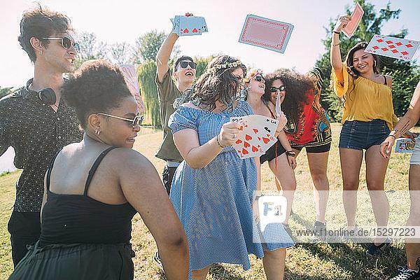 Gruppe von Freunden tanzt  wirft im Park Spielkarten in die Luft