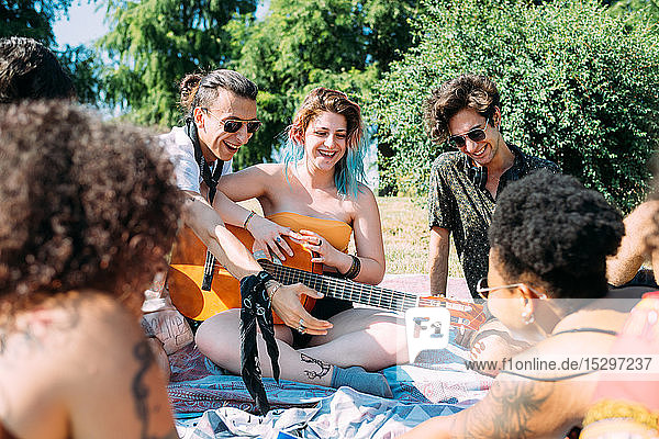 Group of friends relaxing  playing guitar at picnic in park